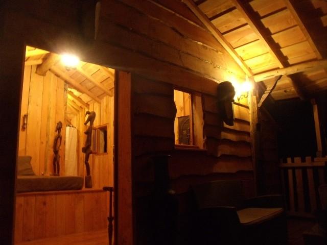 Cabane de charme aquitaine. Terrasse de la case du ruisseau dans une ambiance africaine nocturne